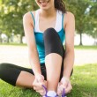Active smiling brunette tying her shoelaces — Stock Photo