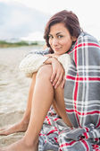 Woman covered with blanket at beach — Stock Photo