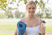 Cheerful blonde woman posing holding an exercise mat — Foto de Stock