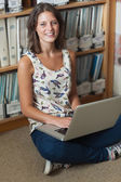 Smiling student against bookshelf with laptop on the floor — Stock Photo