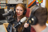 Attractive happy radio host interviewing a guest — Stockfoto