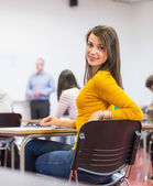 Female with blurred teachers students in classroom — ストック写真