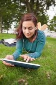 Calm casual student lying on grass using tablet — Stock Photo