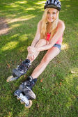 Casual content blonde wearing roller blades and helmet — Stock Photo
