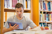 Attractive focused student using tablet and turning page — Stock Photo