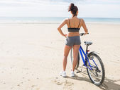 Rear view of a woman with bike on beach — Foto Stock