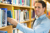 Smiling mature student selecting book from shelf in library — Stock Photo