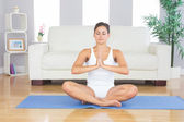Front view of meditating slim woman sitting in lotus position — Stock Photo