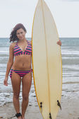 Full length of a bikini woman holding surfboard at beach — Foto Stock