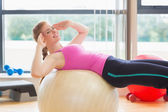 Fit woman working out with exercise ball in fitness studio — Stock Photo
