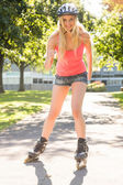 Casual smiling blonde inline skating — Stock Photo