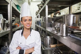 Young cheerful chef standing arms crossed between shelves — Stock Photo