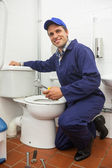 Good looking plumber repairing toilet — Foto de Stock
