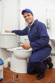 Good looking plumber repairing toilet — Stockfoto