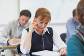Concentrating female mature woman sitting in classroom — Stock Photo