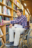 Man in wheelchair selecting book in library — Stock Photo