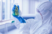 Ccientist in protective suit with hazardous chemical in flask at — Stock Photo