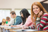 Female student with others writing notes in classroom — Stock Photo