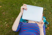 Student lying on grass using tablet — Stok fotoğraf