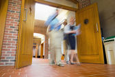 Group of blurred people walking through open doors — Stock Photo