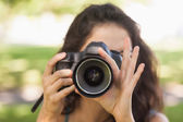 Front view of young brunette woman taking a picture — Stock Photo