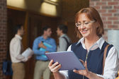 Amused smiling mature woman using her tablet — Stock Photo