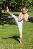Young sporty woman practicing yoga standing on a lawn — Stock Photo