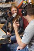 Attractive smiling radio host interviewing a guest — Stock Photo