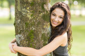Casual cheerful brunette embracing a tree looking at camera — Stock Photo