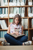 Female student against bookshelf reading a book on the library f — Stock Photo