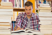 Handsome student studying between piles of books — Stock Photo