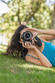 Young brunette woman lying on a lawn taking a picture — Stock Photo