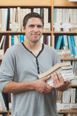 Mature student posing in library holding a pile of books — Photo