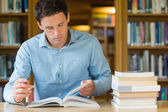 Serious mature student studying at library desk — Stock Photo