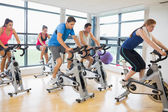 Determined people working out at spinning class — Stock fotografie