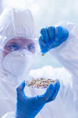 Scientist in protective suit with sprouts in laboratory — Stock Photo