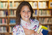 Close-up of a smiling female student in the library — Стоковое фото