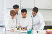 Serious scientists using tablet PC in the lab — Stock Photo
