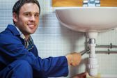 Handsome smiling plumber repairing sink — Stock Photo