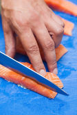 Close up of hand slicing salmon with sharp knife — Stock Photo
