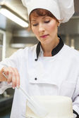 Pretty concentrating head chef finishing a cake with icing — Stock Photo