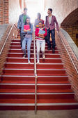 College students walking down stairs in college — Stock Photo