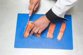 Chef slicing raw salmon with sharp knife — Stock Photo