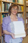 Mature female librarian posing holding a pile of books — Stock Photo