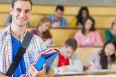 Macho sorridente com os alunos sentados na sala de aula — Fotografia Stock