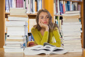 Thoughtful pretty student studying between piles of books — Stock Photo