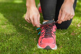 Close up of sporty woman tying her shoelaces — Stock Photo