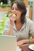 Young woman using laptop while eating apple — Stock Photo