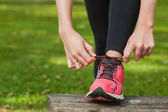 Young woman tying the shoelaces of her running shoes — Stock Photo