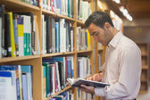 Intellectual man reading a book standing in library — Stock Photo